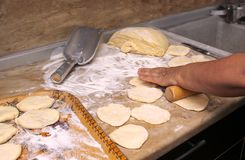 Old woman baking pies in her home kitchen. Grandma cooks pies. Home cooked food. omemade mold cakes of the dough in the ederly wom. En`s hands. The process of Royalty Free Stock Photography
