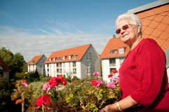 Old woman on the balcony. Old woman sunbathes on the balcony royalty free stock photography