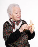 Old woman with banana. On a white background Royalty Free Stock Photo