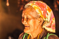 Old woman with beads in Nepal. Dolpo, Nepal - circa May 2012: Old smiling woman with short grey hair and colourful headcloth wears brown shirt looks to left in Royalty Free Stock Photos