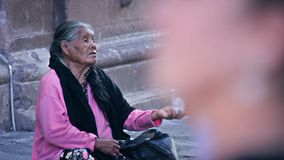 Old woman begging on the sidewalk, people passing around. GUANAJUATO, MX 2016 (ILLUSTRATIVE IMAGE): Old woman begging on the sidewalk, people passing around stock video