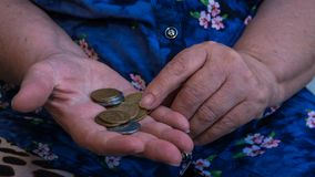 Old woman begs for alms. Closeup of money and coins in hand of poor woman royalty free stock image