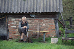 The old woman on the bench in the countryside. RUSSIA, TULA OBLAST AUGUST 2013:The old woman on the bench in the countryside Royalty Free Stock Photos