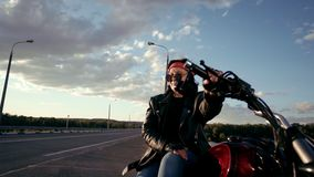 Old woman biker in a leather jacket and gloves sitting on his motorcycle. There`s an empty highway in the background