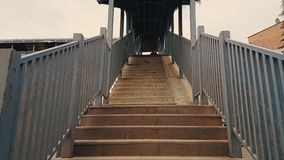 Old woman with black coat and hijab walking up the stairs of the footbridge stock video footage