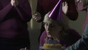 Old woman blowing out cake candles on 100 birthday party, volunteers support stock footage