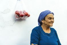 An Old Woman With Blue Dress Near Of The White Wall. Seferihisar,Izmir,Turkey- August 20, 2017: An old woman with blue dress is standing near of the white wall Royalty Free Stock Images