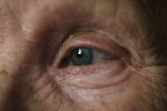 Old woman blue-gray eye closeup photo stock images