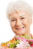An old woman with bouquet of flowers. Stock Photography