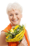 An old woman with bouquet of flowers. Royalty Free Stock Images