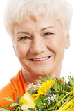 An old woman with bouquet of flowers. Stock Photos