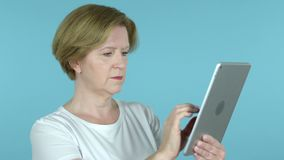 Old Woman Browsing Interne on Tablet, Blue Background stock video footage