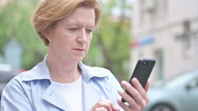 Old Woman Browsing Smartphone Standing Outdoor stock video
