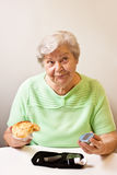 Old woman with bun and blood glucose meter Stock Photo