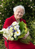 Old woman with a bunch of flowers Stock Images