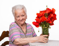 Old woman with bunch of poppies Royalty Free Stock Images