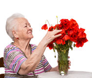 Old woman with bunch of poppies Stock Photography