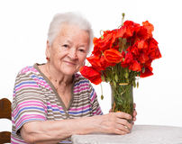 Old woman with bunch of poppies Royalty Free Stock Photo