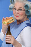 Old woman with a burger and beer Stock Image