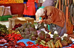Old Woman Buying Vegetables in the Market. Crooked elderly woman buying her vegetables in a mexican market (San Miguel de Allende Royalty Free Stock Photo