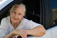 Old woman in the car. Old smiling woman in the car Stock Images
