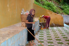 Old woman carrying water Stock Images