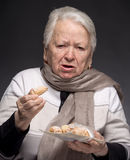 Old woman choking with cookie Stock Photography