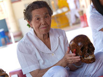Old woman cleaning skull Royalty Free Stock Image