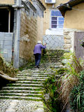 An old woman climbing the stairs Stock Images