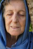 An old woman with closed eyes and covered head. Royalty Free Stock Photography