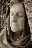 An old woman with closed eyes and covered head. Royalty Free Stock Photo