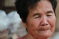 Old woman closes one's eyes Stock Photo