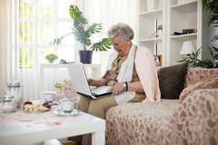 Old woman connecting with her family. On her laptop stock images