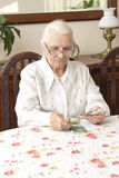 The old woman counting money while sitting at the table. Pension. Old woman counts the money Royalty Free Stock Image