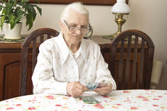 The old woman counting money while sitting at the table. Pension. Old woman counts the money Stock Photos