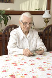 The old woman counting money while sitting at the table. Pension. Old woman counts the money Stock Images