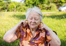 Old woman  covers her ears with  hands Royalty Free Stock Image