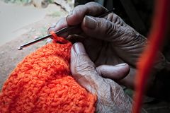 Old woman crocheting. Close up of old woman`s hands crocheting with orange yarn, a shade of life stock photo