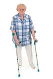 Old woman with crutches. Elderly woman walking on crutches - isolated on white Royalty Free Stock Image