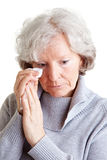Old woman crying with handkerchief. Old senior woman crying and drying her tears with a handkerchief Royalty Free Stock Image