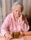 Old woman with cup of tea Stock Photography