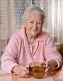 Old woman with cup of tea Royalty Free Stock Photography