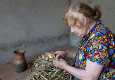 The old woman cuts an onions at itself Stock Photography