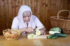 The old woman cuts  vegetable marrow Royalty Free Stock Photos