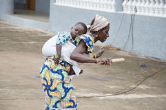 Old woman dancing with a child on the back. Royalty Free Stock Photography