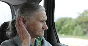 7d6a5722be An old woman with deep wrinkles and gray hair rides in the back seat of the