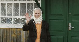 An old woman with deep wrinkles in a scarf stands and waves her hand on the background of a village house. Poor granny smiles stock video