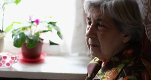 An old woman with deep wrinkles sits near the window. Sad old woman is resting at home. Side view stock video