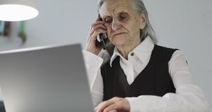 An old woman with deep wrinkles is talking on a mobile phone while sitting at a laptop. Grandma works in the office stock footage