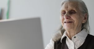 Old woman with deep wrinkles talking on the video connection. Business grandmother works at a laptop stock footage